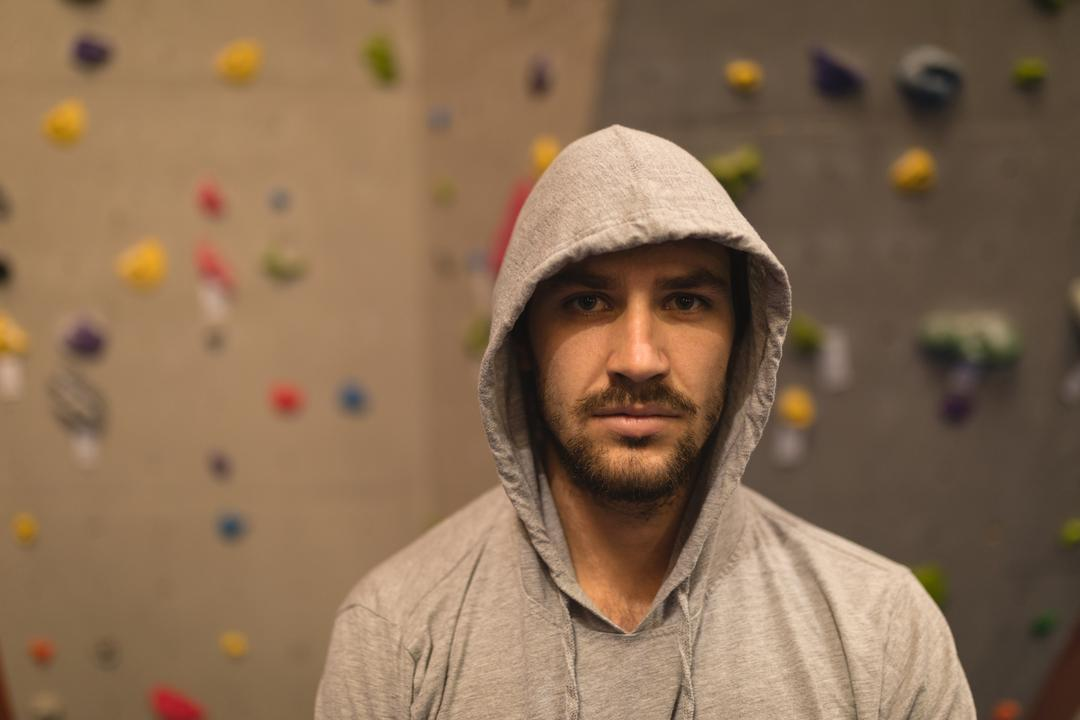 Portrait of male athlete wearing hooded shirt while standing by climbing wall in gym
