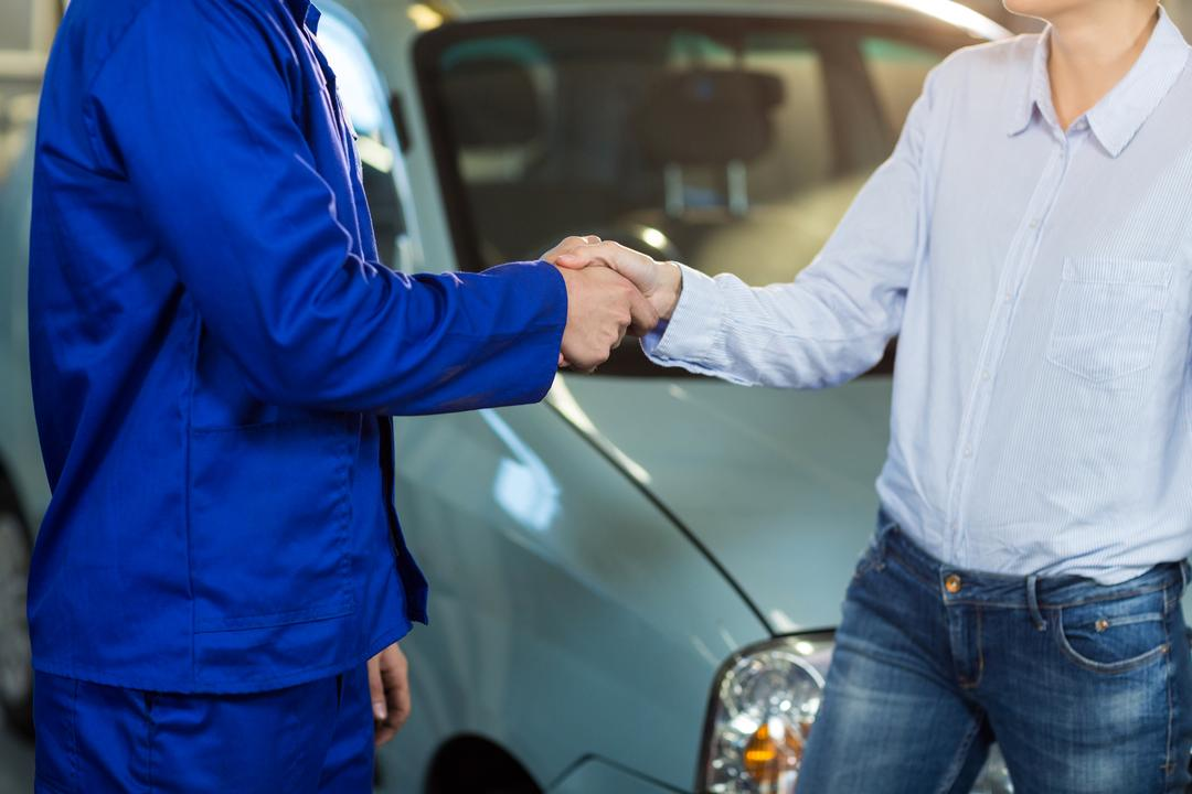 Mid-section of customer shaking hands with mechanic in repair garage