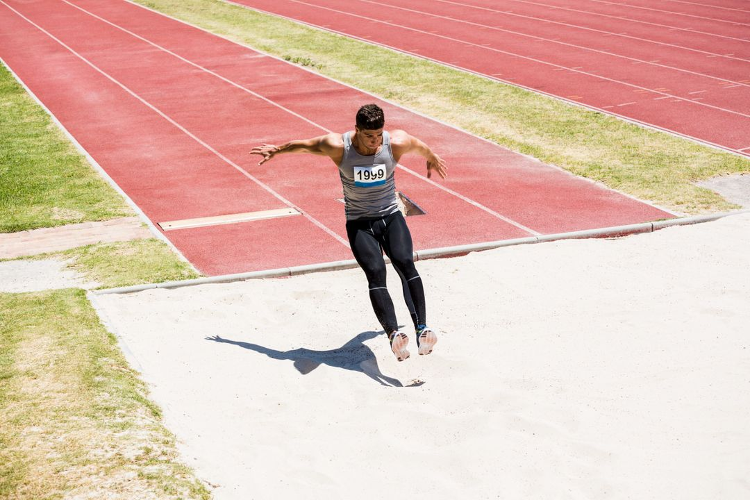 Athlete performing a long jump during a competition Free Stock Images from PikWizard