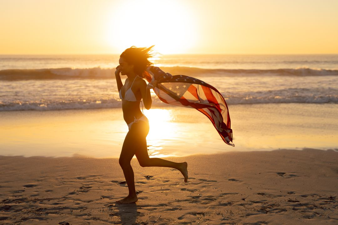Young woman with an American flag running on the beach