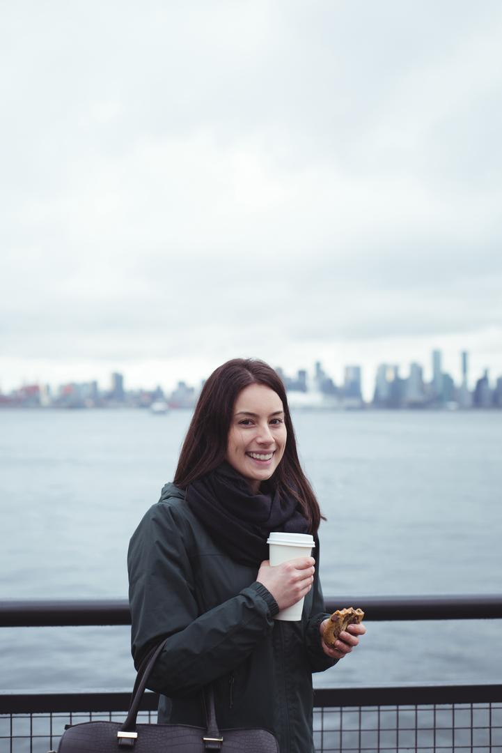 Portrait of woman holding food and drink while standing by railing against sea in city