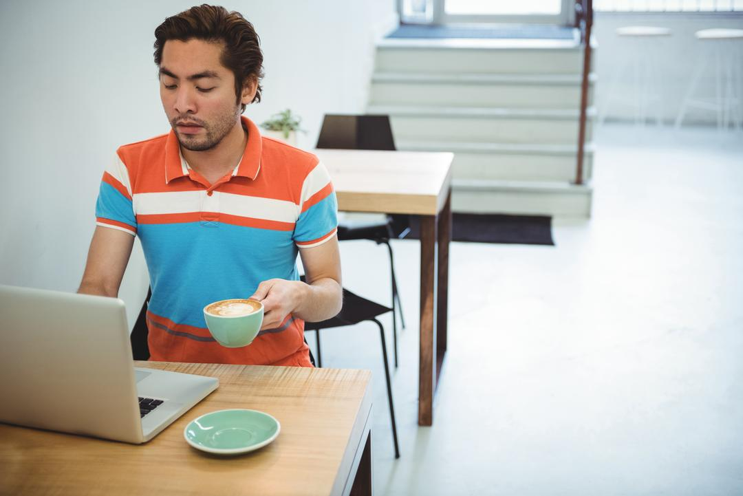 Man using laptop while having cup of coffee in coffee shop