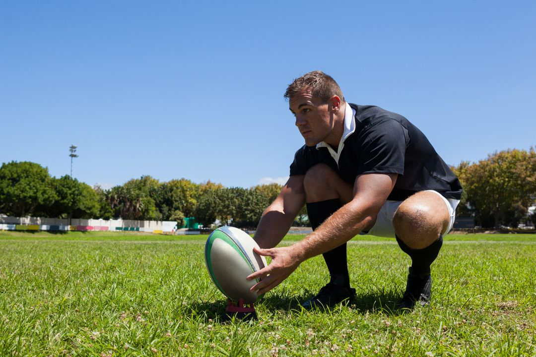 Rugby player holding ball while kneeling on grassy field against clear sky