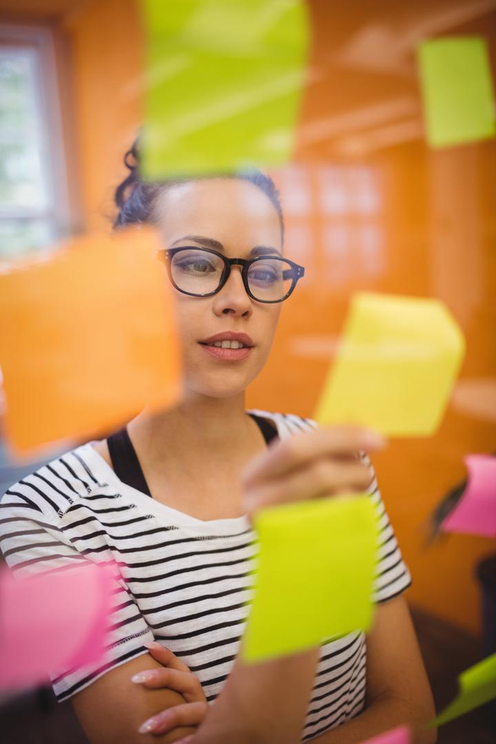 Beautiful female executive reading sticky notes in office