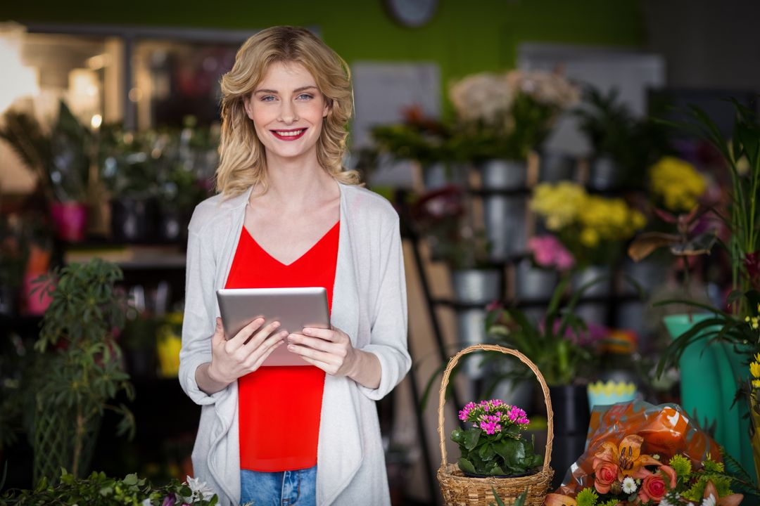 Portrait of happy female florist holding digital tablet in flower shop Free Stock Images from PikWizard