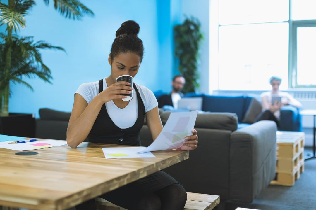 Female executive reading document while having coffee in office