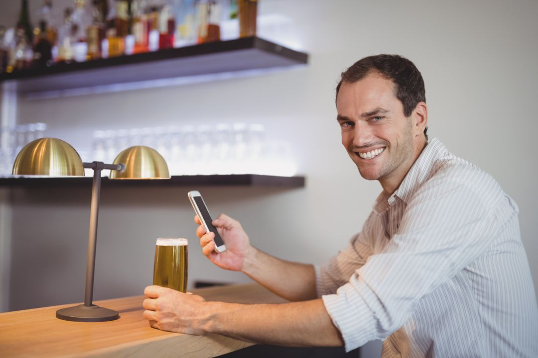 Man using mobile phone while having beer in restaurant Free Stock Images from PikWizard