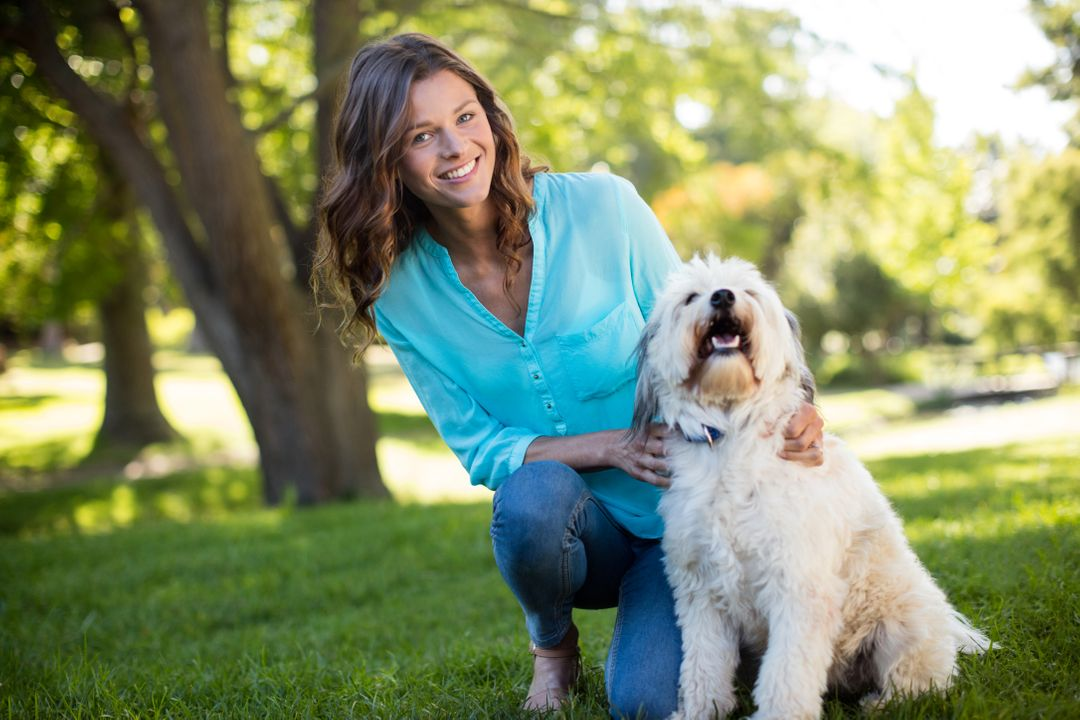 Portrait of woman with dog in park on sunny a day Free Stock Images from PikWizard
