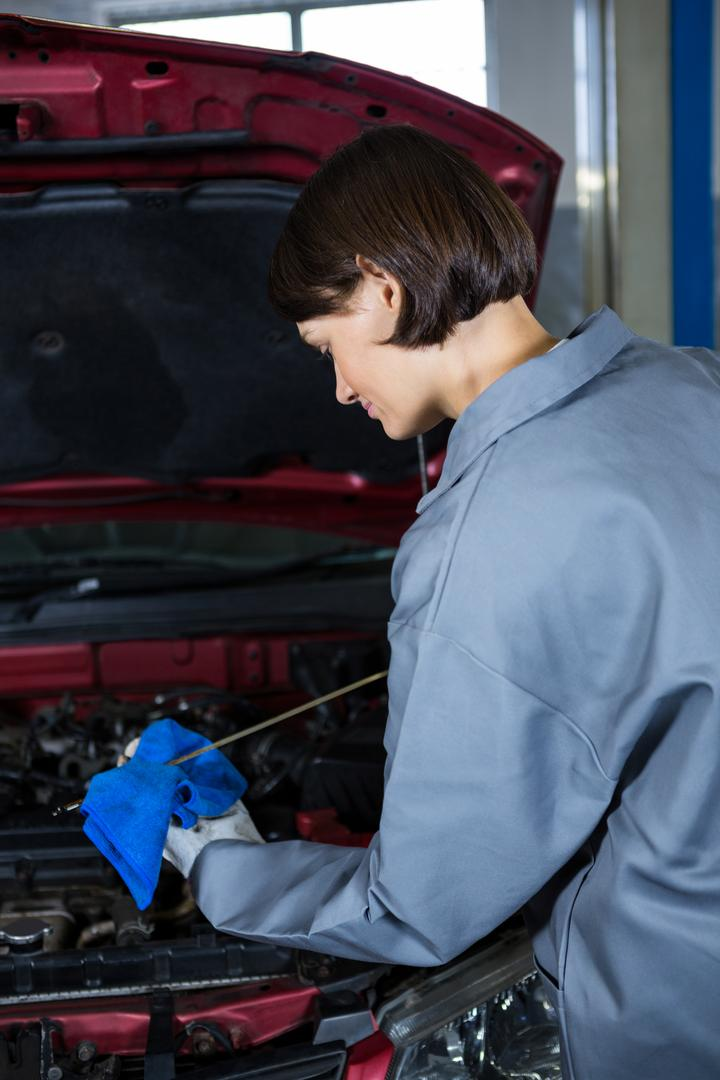 Female mechanic checking the oil level in a car engine with a dipstick at repair garage