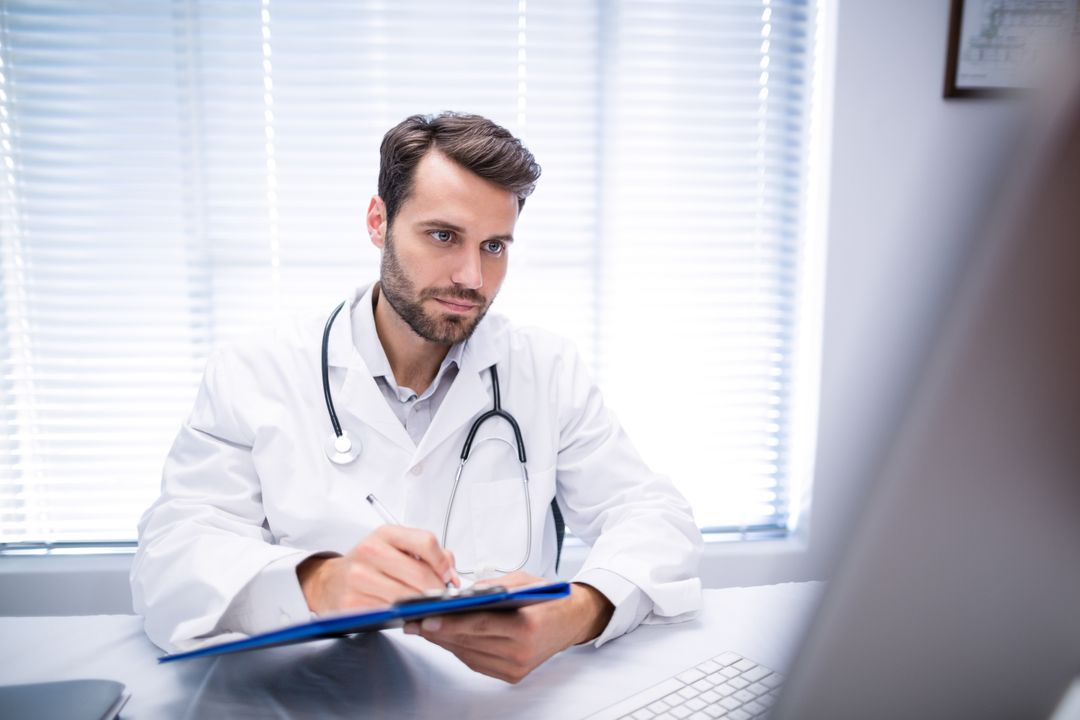 Male doctor writing on clipboard while working on personal computer in clinic Free Stock Images from PikWizard