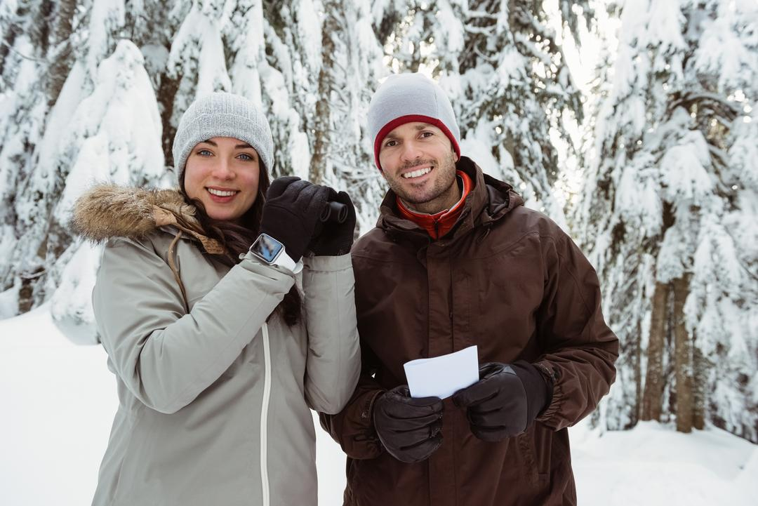 Portrait of skier couple holding a binocular and address card on snow covered mountain