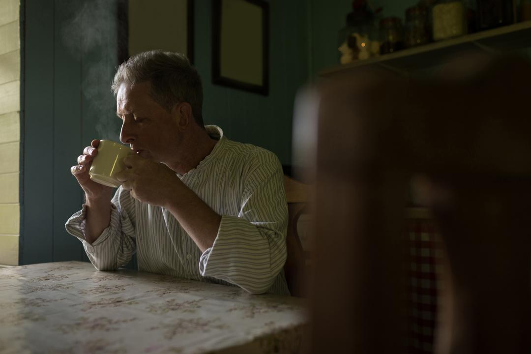 Senior man having coffee in kitchen at home