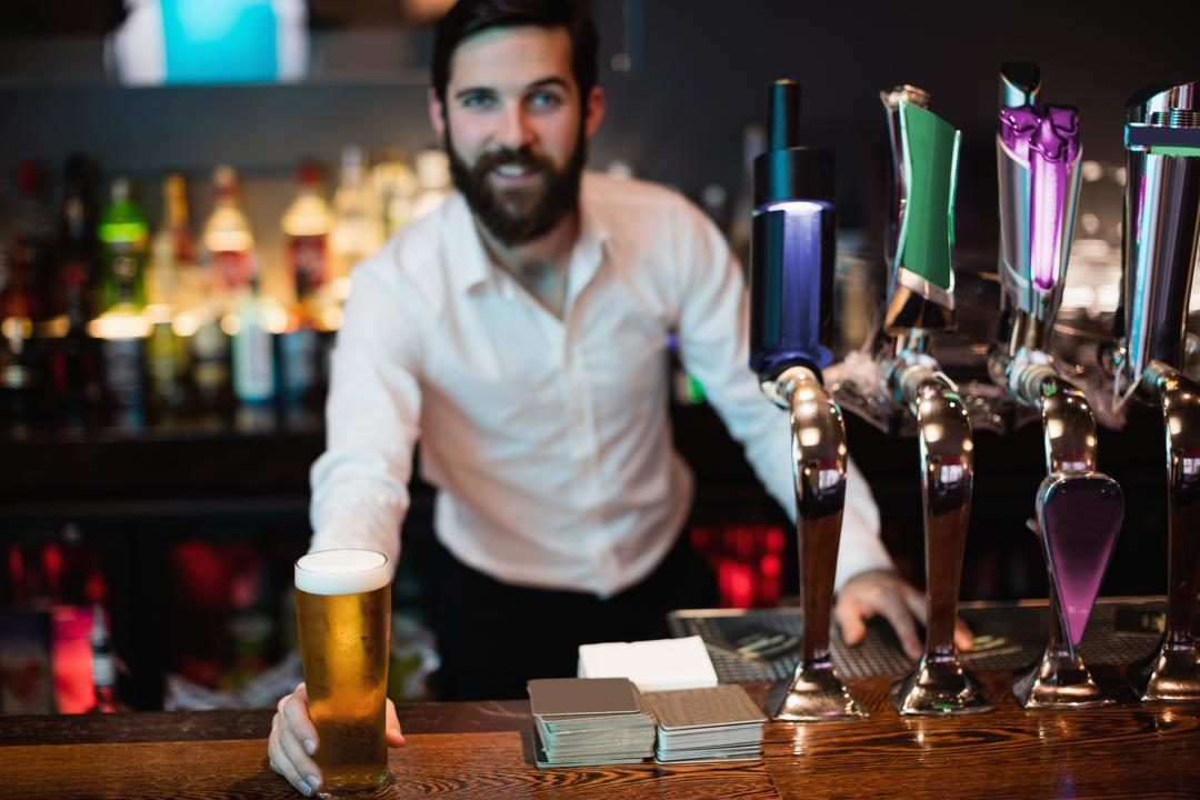 Portrait of bartender holding glass of beer at bar counter Free Stock Images from PikWizard