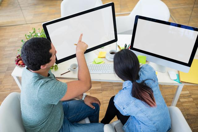 Male and female graphic designers interacting over computer