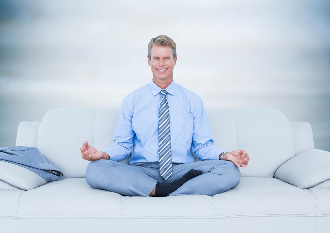 Digital composite of Business man meditating on couch against blurry grey wood panel