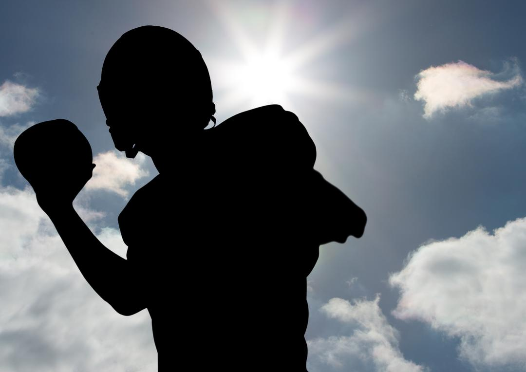 Silhouette of player throwing a ball against sunny sky in background