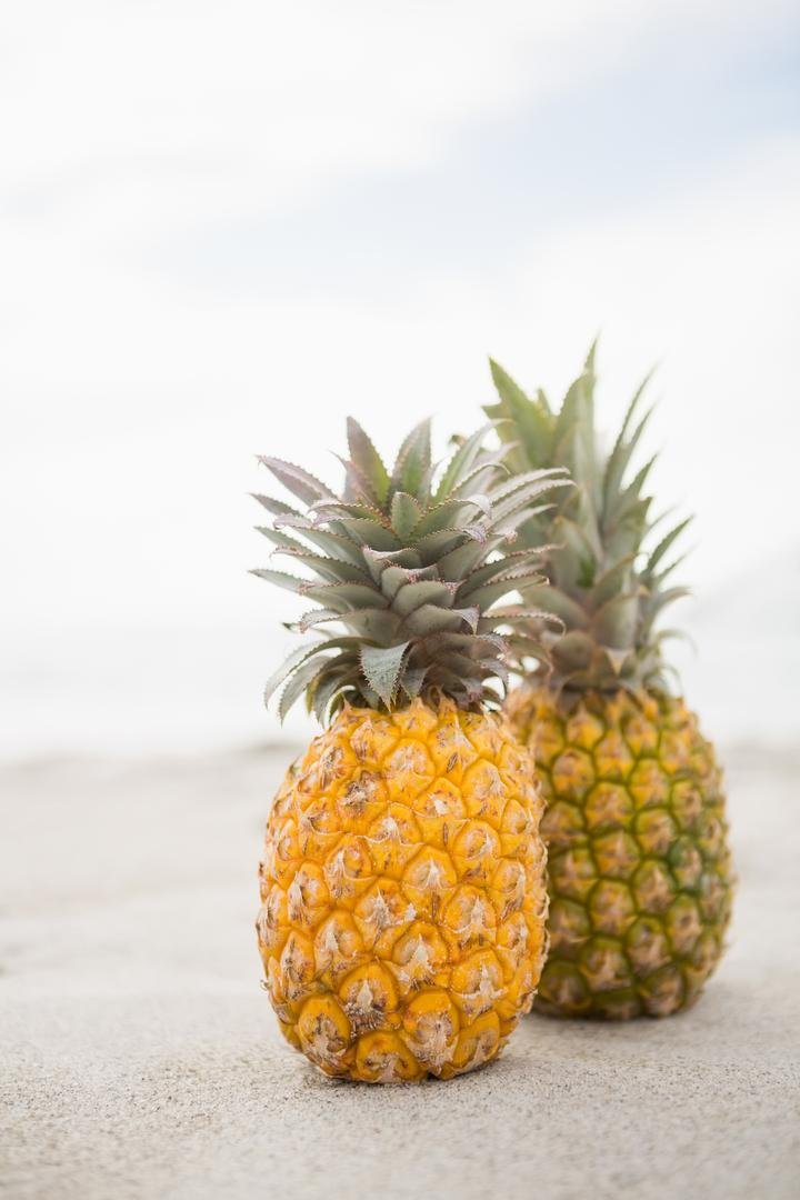 Two pineapples kept on the sand at tropical beach
