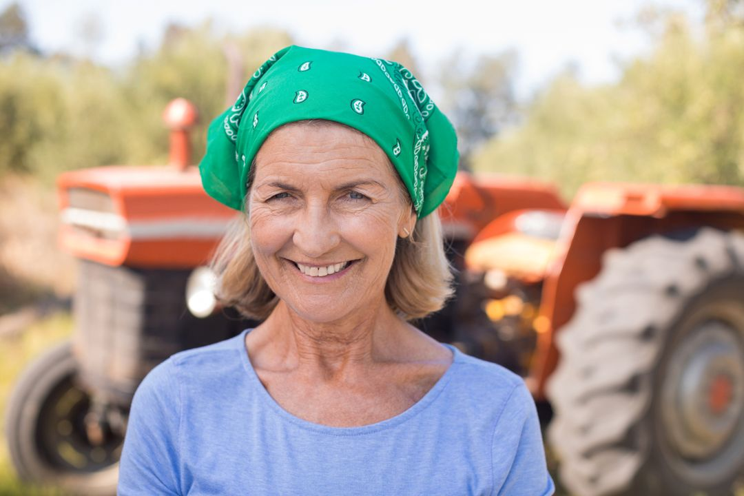 Portrait of happy woman standing against tractor in olive farm on a sunny day