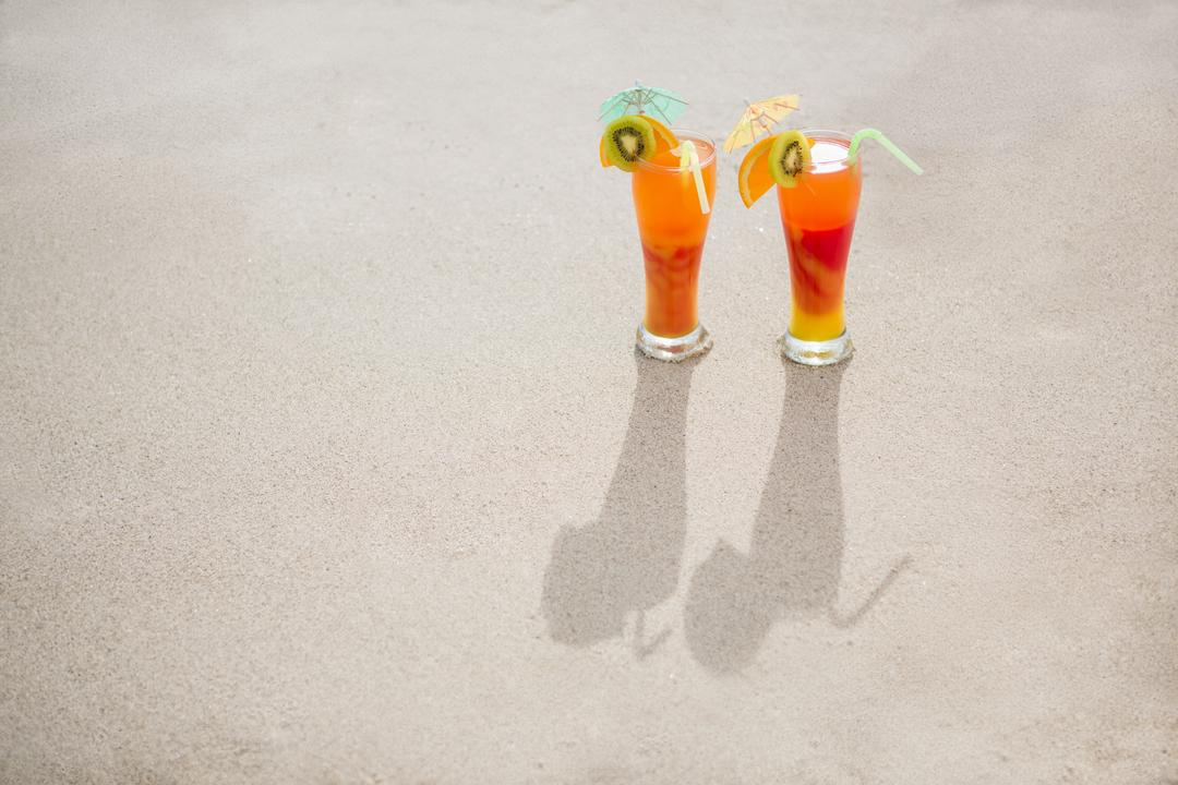 Overhead view of two glasses of cocktail drink kept on sand at tropical beach Free Stock Images from PikWizard