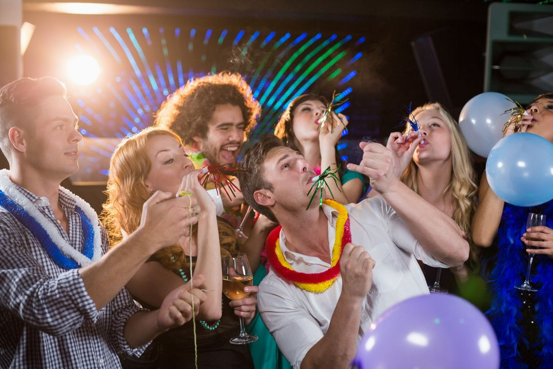 Group of smiling friends blowing party horn in bar Free Stock Images from PikWizard