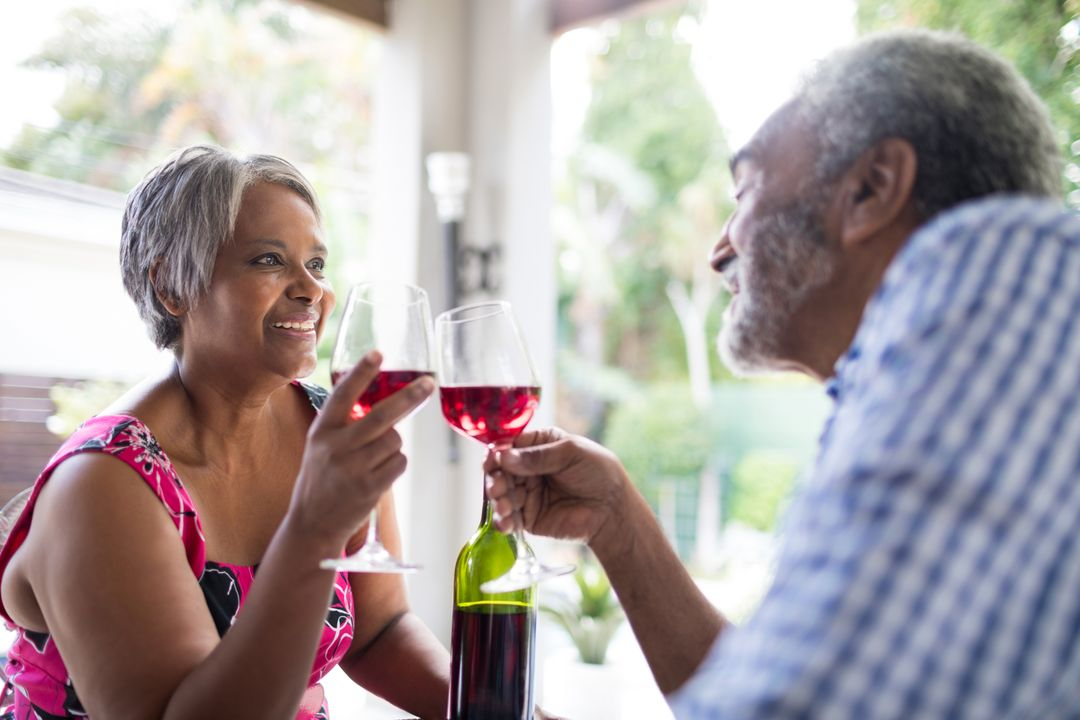 Smiling couple toasting wineglasses while sitting in yard Free Stock Images from PikWizard