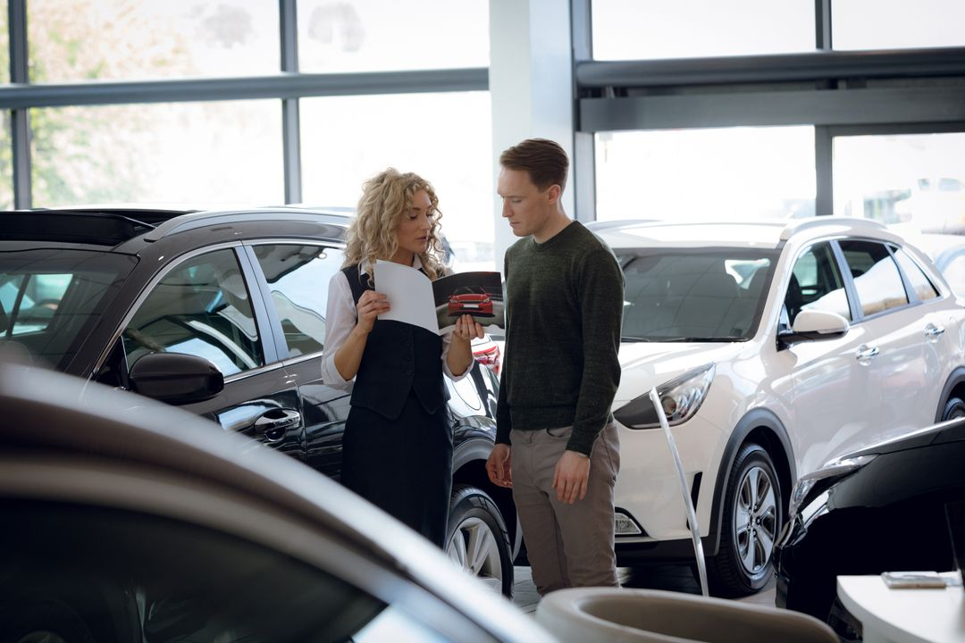 Saleswoman showing brochure to male customer while standing by cars in showroom Free Stock Images from PikWizard