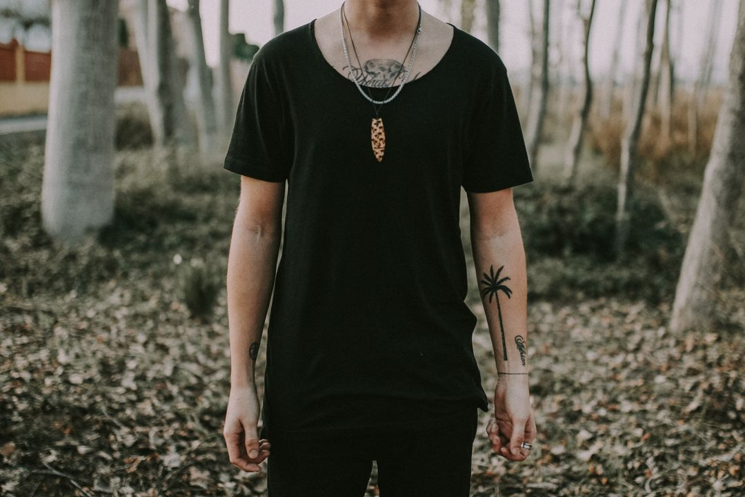 Man standing in forest with tattoos