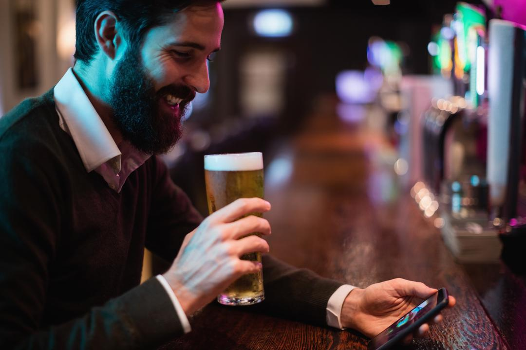 Man looking at mobile phone while having glass of beer in bar counter
