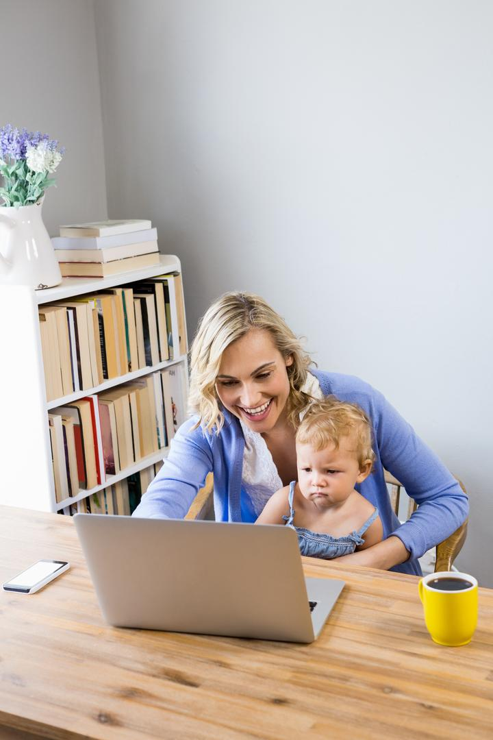 Mother and baby sitting at table and using laptop at home