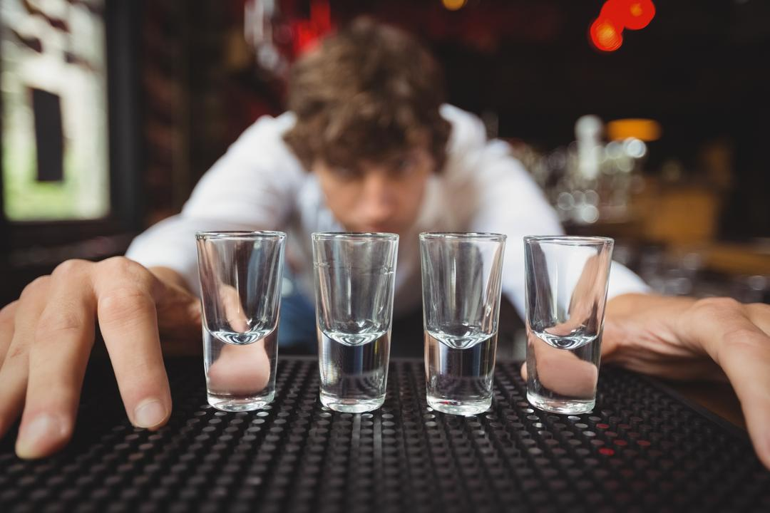 Bartender preparing and lining shot glasses for alcoholic drinks on bar counter