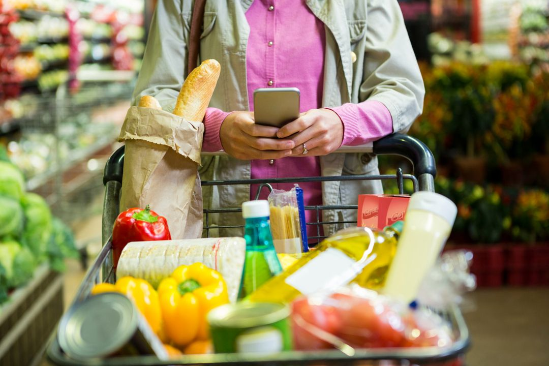 Woman using mobile phone while shopping in supermarket Free Stock Images from PikWizard