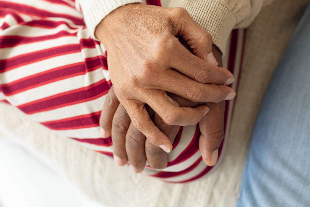 Digital composite of an old African-American couple hands resting on top of each other