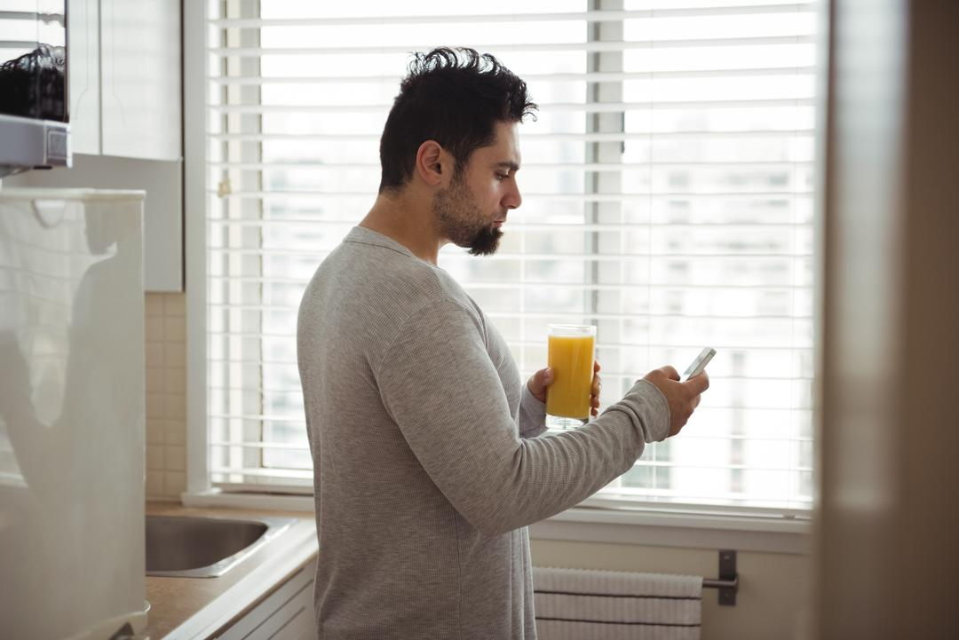 Man using mobile phone while having juice in kitchen at home