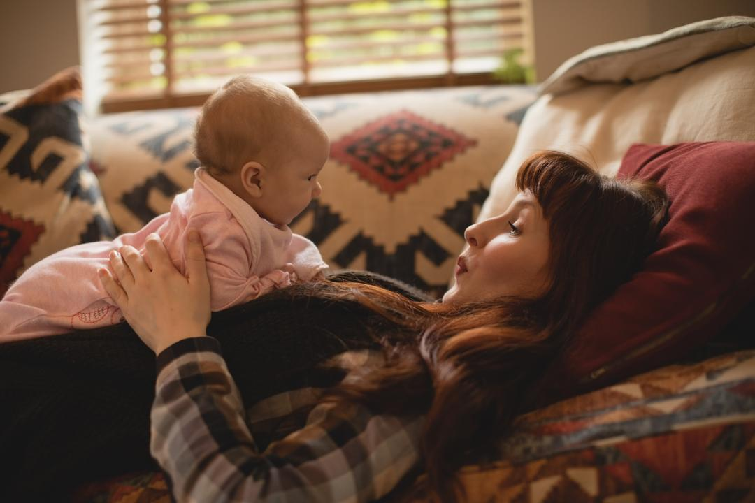 Woman laying on a sofa with her baby