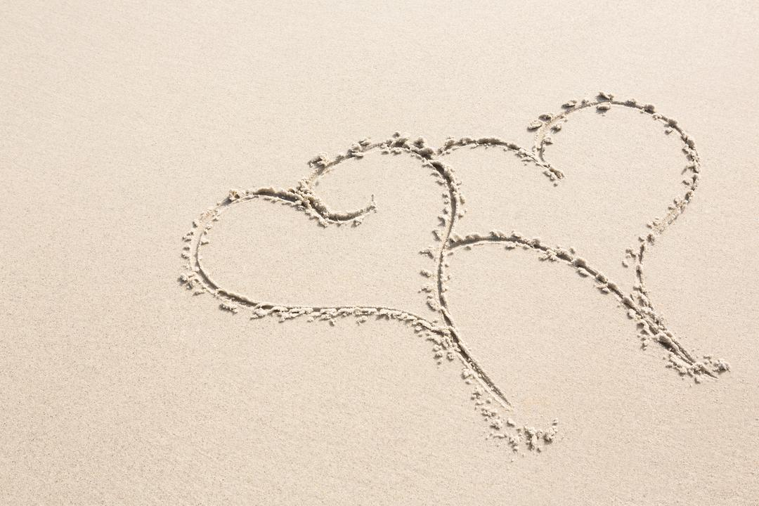 Two heart shapes drawn on sand on beach
