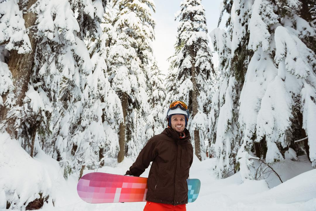 Man standing and holding a snowboard on snow covered mountain