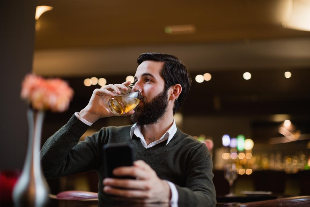 Man holding mobile phone and having a drink in bar Free Stock Images from PikWizard