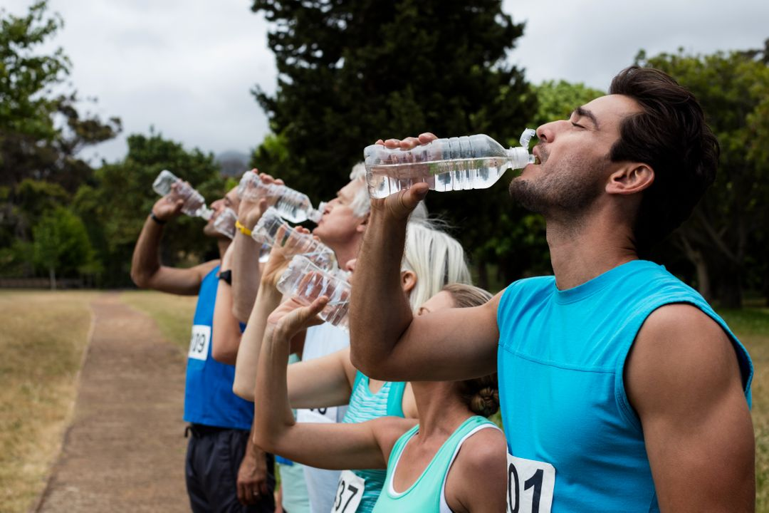 Athletes drinking water in park on sunny a day