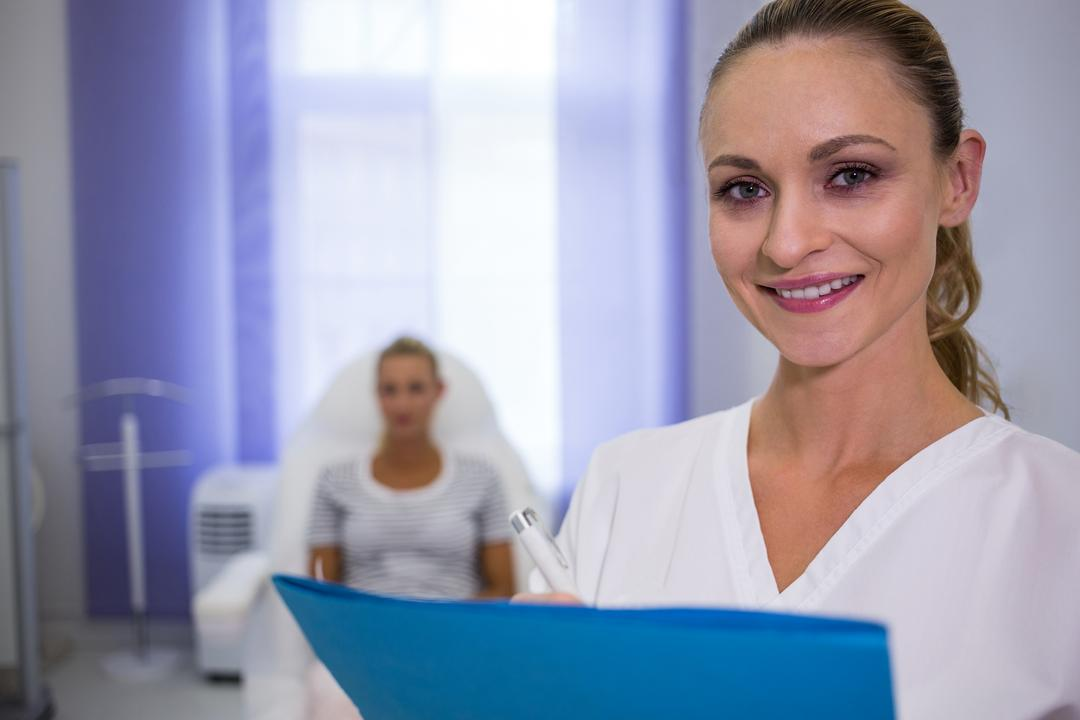 Portrait of smiling female doctor holding medical reports