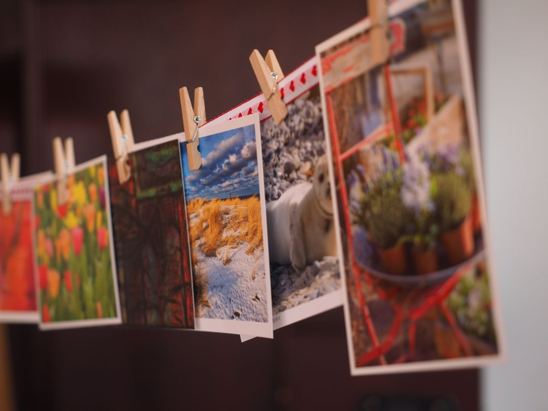 six small pieces of colourful art hung on a string with clothes pegs
