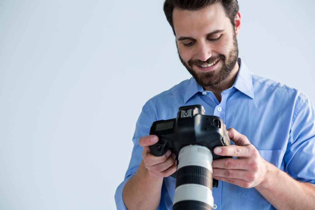 Male photographer reviewing captured photos in her digital camera at studio
