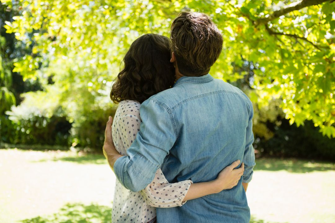 Rear view of couple embracing each other in garden on a sunny day Free Stock Images from PikWizard