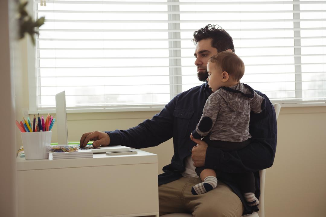 Father holding his baby while using laptop at desk at home