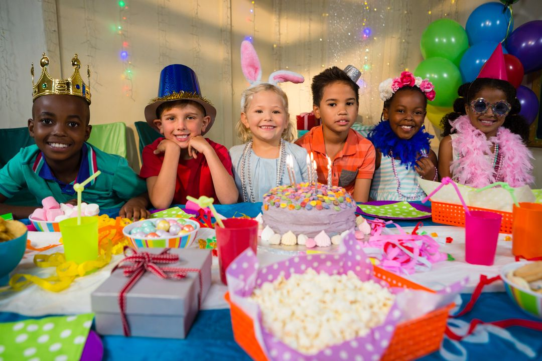 Portrait of smiling children at table during birthday party Free Stock Images from PikWizard