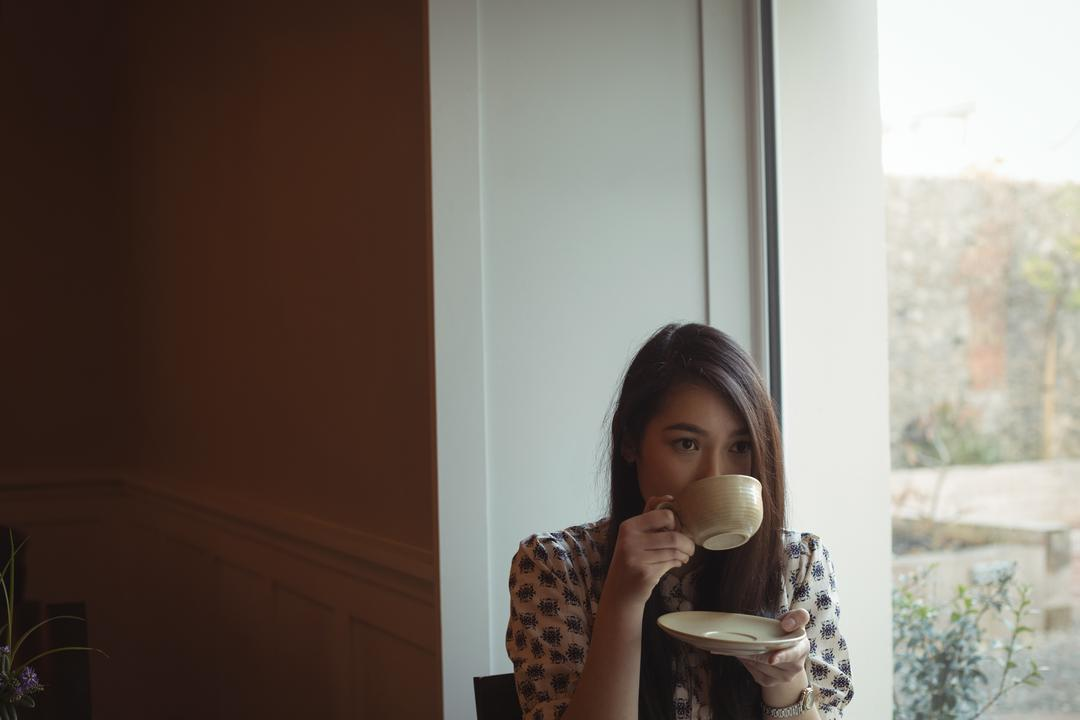 Beautiful woman having cup of coffee near window at café