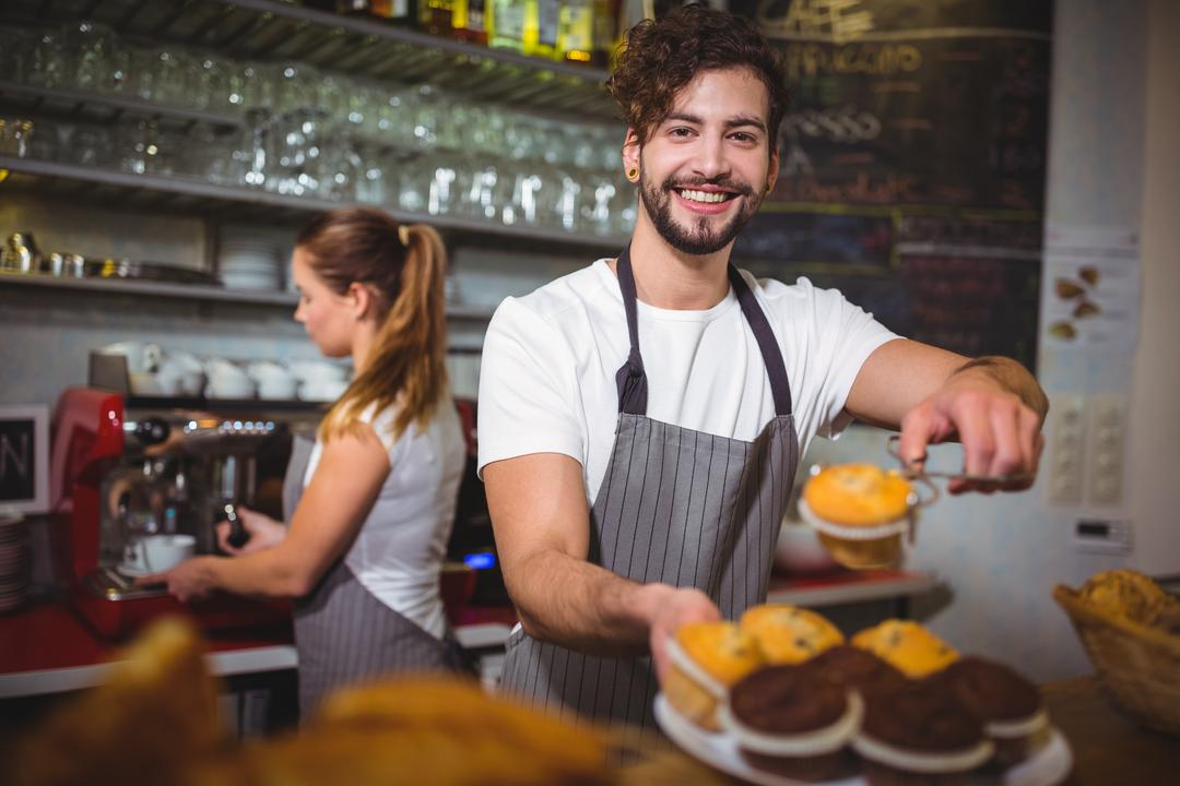 Portrait of waiter holding a plate of cup cake at counter in café Free Stock Images from PikWizard
