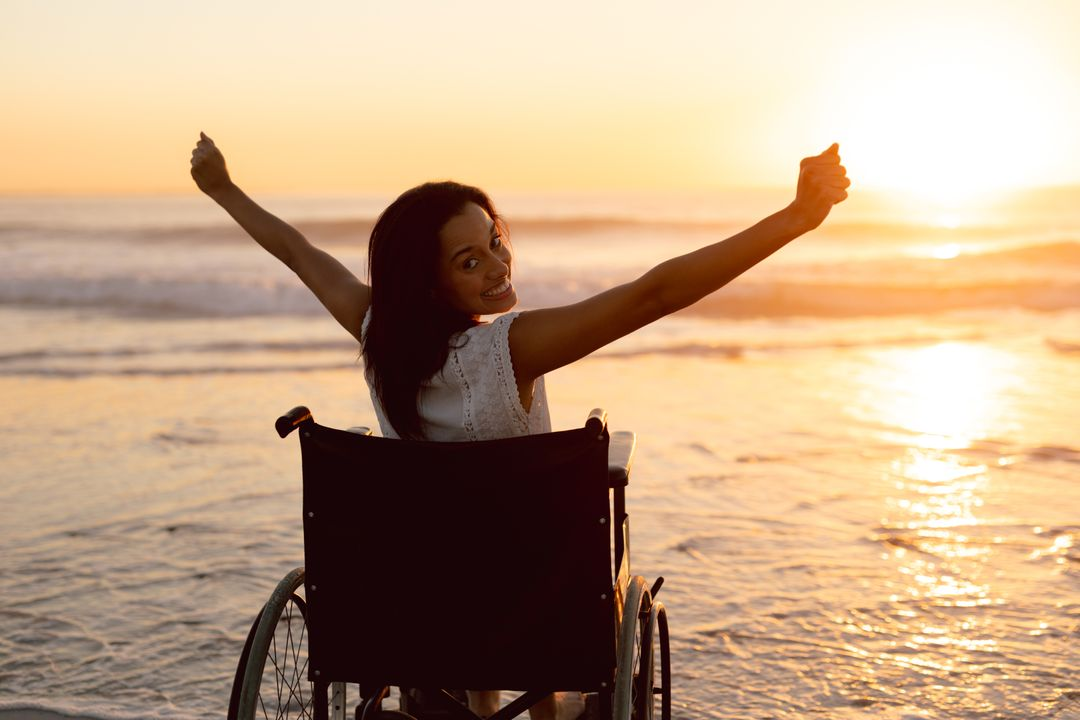 Portrait of disabled woman with arms outstretched on the beach Free Stock Images from PikWizard