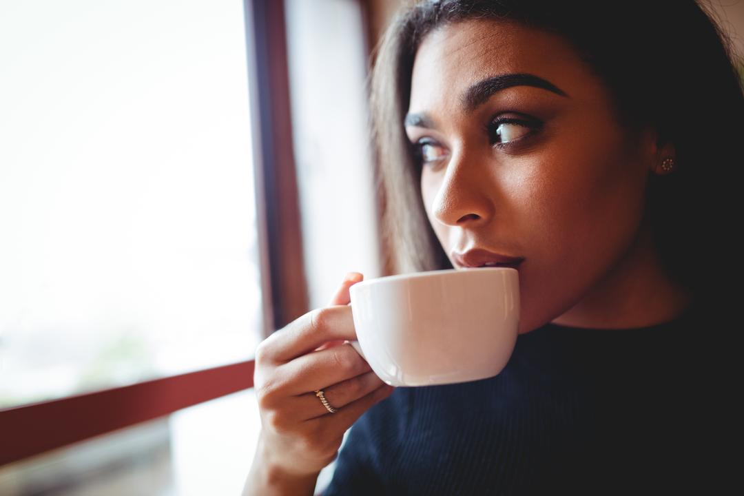 Thoughtful woman having a cup of coffee in cafe