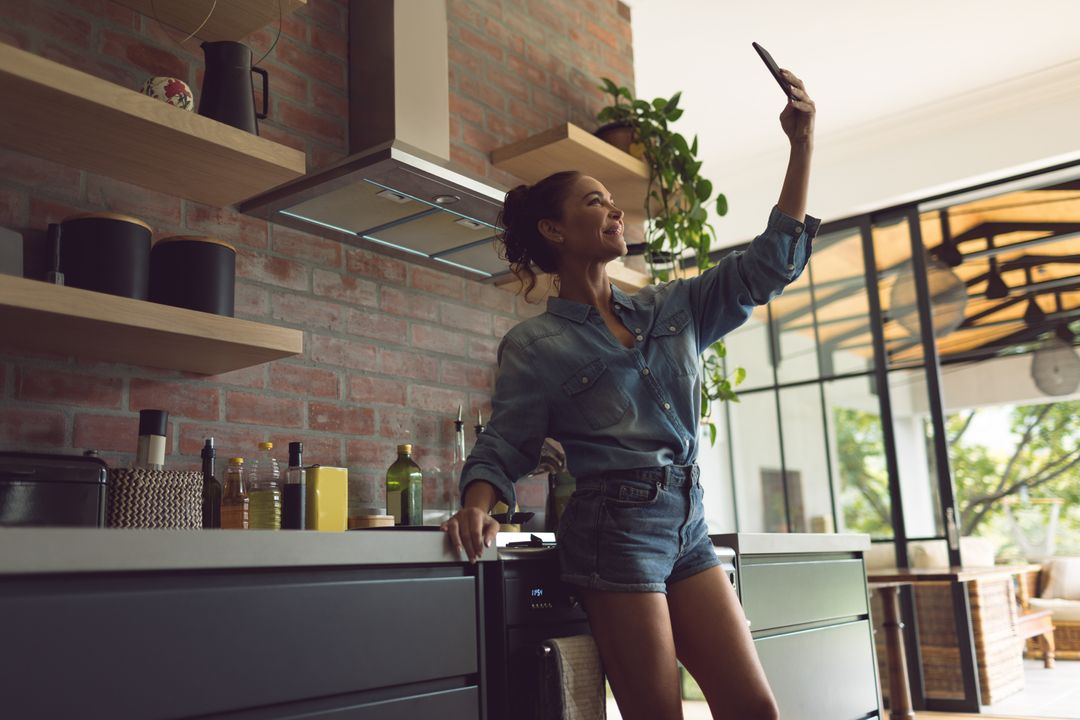 Beautiful woman taking selfie with mobile phone in kitchen at comfortable home