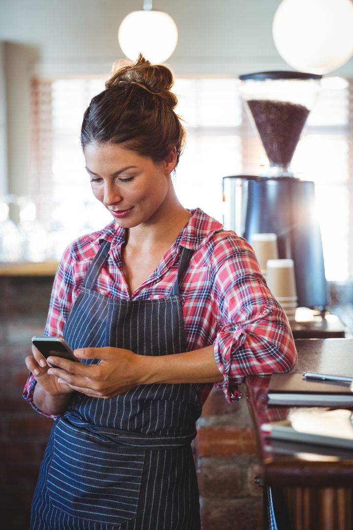 Waitress using a smartphone in a cafe Free Stock Images from PikWizard